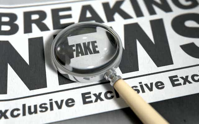 """A newspaper showing the words """"breaking news"""" with a magnifying glass over the word """"fake""""."""