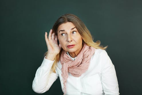 Woman holding her hand up to her ear to hear better.