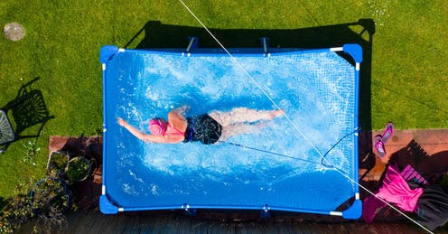 A woman swims in a garden paddling pool.