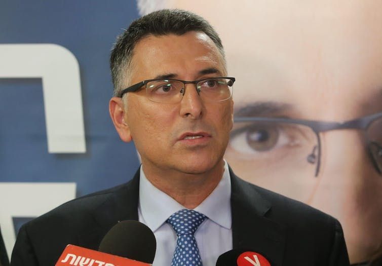 Man with glasses, wearing a suit and tie, speaking in front of a poster with a close-up of his own face.