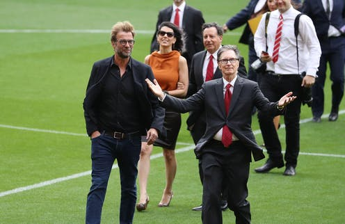 A group of men in suits and one woman walking across a football pitch.