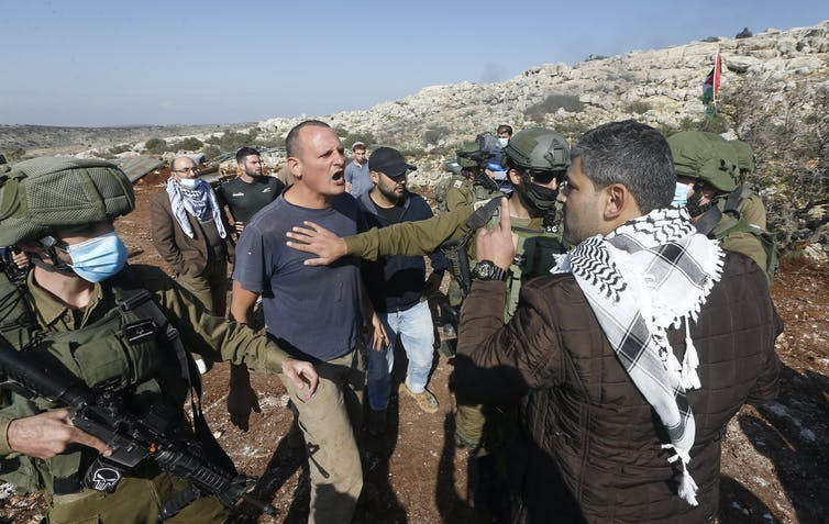 A Palestinian man and an Israeli man argue, with armed Israeli soldiers looking on.