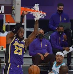 Joueur de basket se suspend au panier.