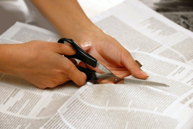 Hands cutting a newspaper.