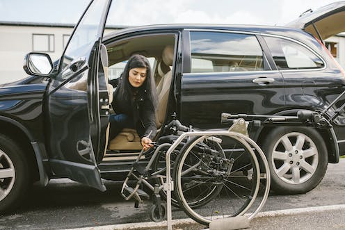 A woman holds a wheelchair next to a car