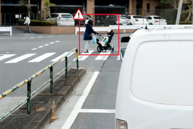 A red alert box around a women on a zebra crossing pushing a pram