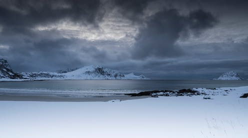Dark clouds form over a snowy landscape near the ocean