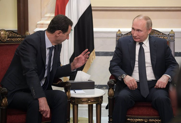 Bashar as-Assad and Vladimir Putin seated and talking