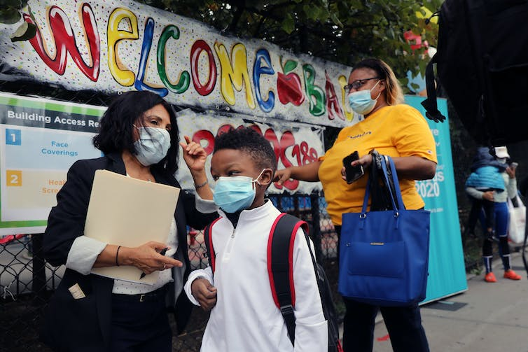 A group of school children and teachers wearing masks walk to school.