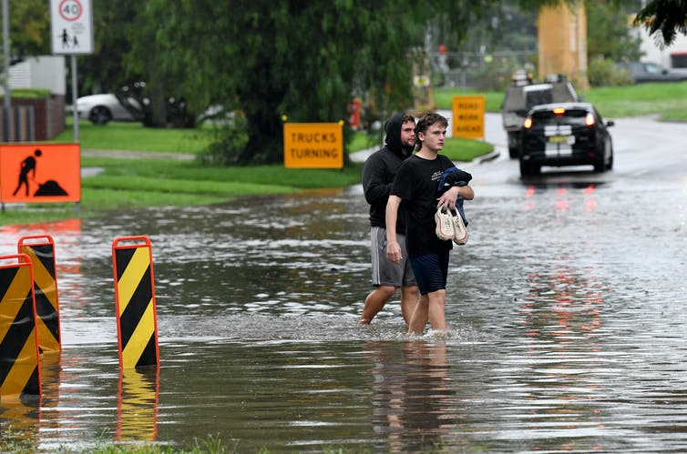 two men stand in floodwaters