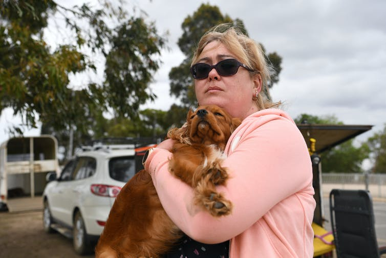 woman holds dog