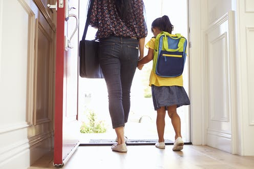 Mother and daughter with school bag on walking out the door.