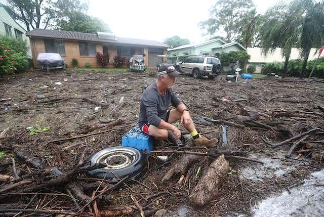 man looks at flood damage