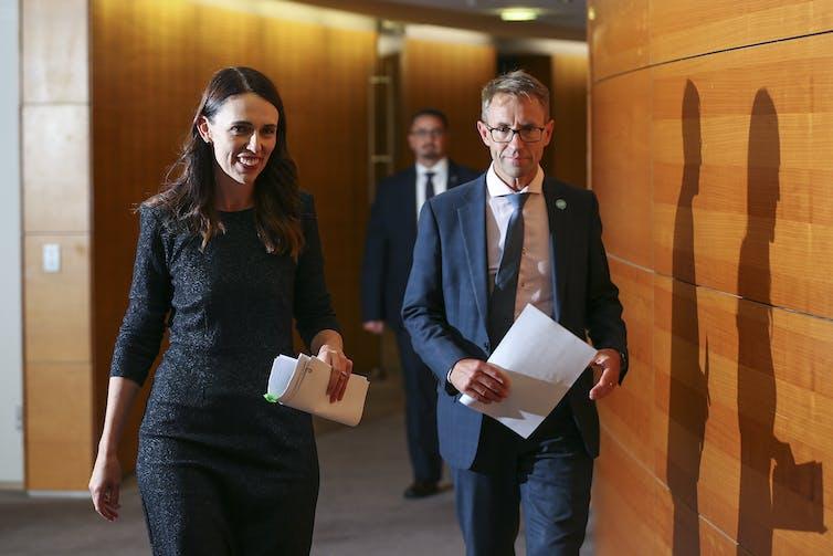 Jacinda Ardern and Ashley Bloomfield walking together in a parliamentary corridor