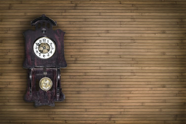 An old pendulum clock with a wooden wall behind.