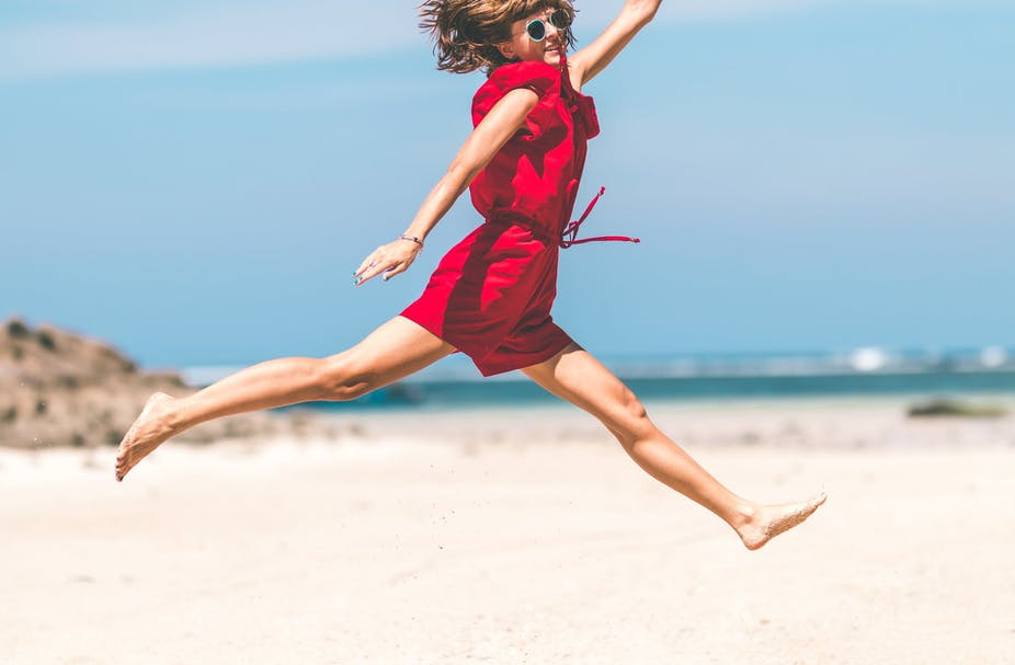 Woman in red jumpsuit jumping at the beach.