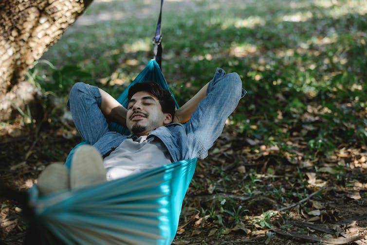 Man lying in a green hammock outside under a tree.