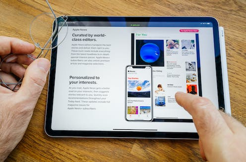 A tablet device showing Apple news and a user's fingers pointing to a news item.