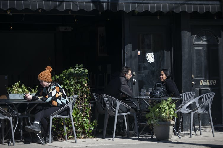 Customers sit on a patio at a bar.