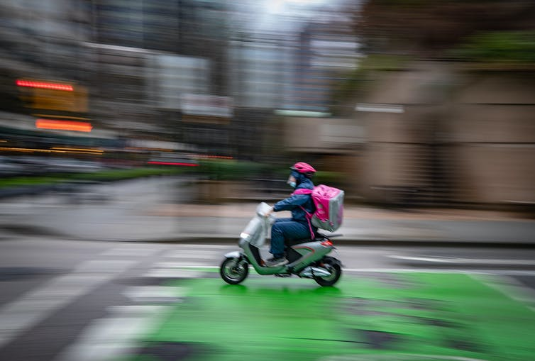 A food delivery worker rides an electric bike