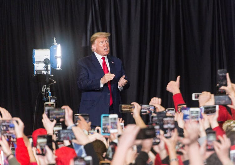 Donald Trump in front of a crowd holding up smartphones