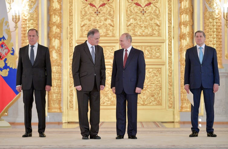 Putin and another man in a suit look at each other intensely, flanked by two other serious-looking men, against a gilded backdrop