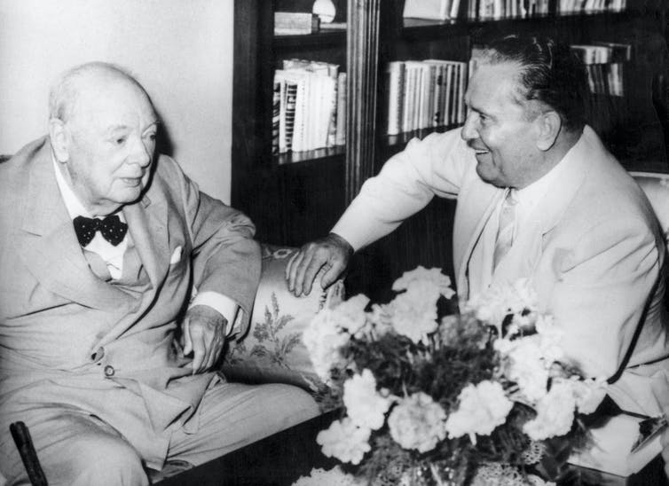 Black-and-white image of a very elderly Churchill sitting and laughing with a younger Tito
