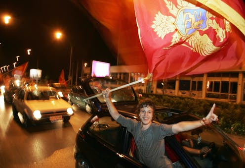 Young man waving a Montenegrin flag out the window of a car and smiling broadly