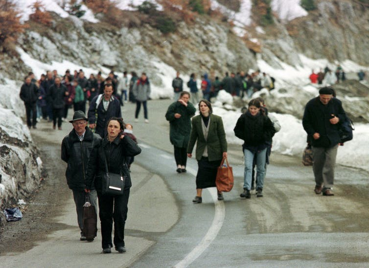 People walk on a mountainous road, wearing backpacks and carrying language; there is snow on the ground