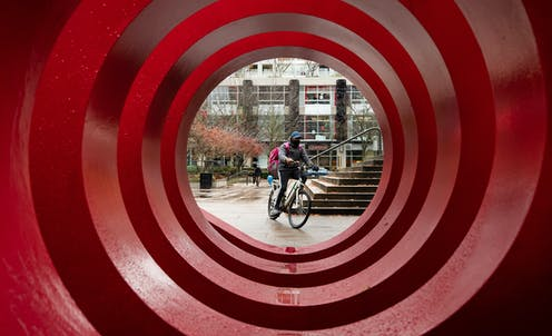 A food delivery worker wearing a face mask is framed by the red circles of a large public art installation.