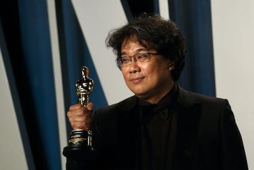 Korean man dressed in black holds Oscar trophy.