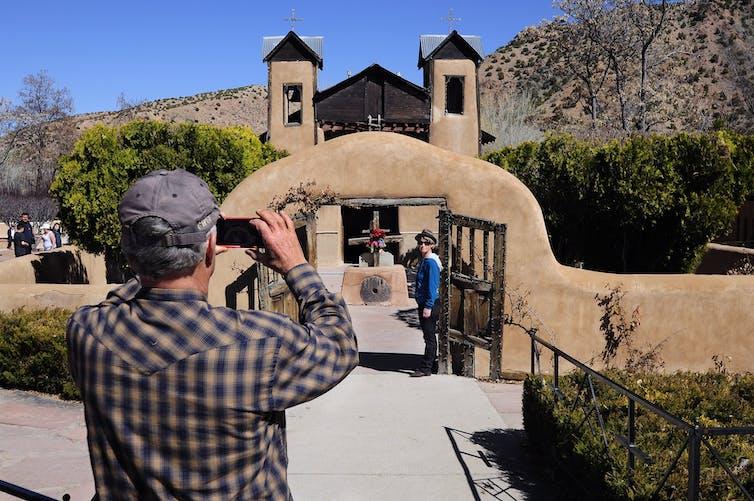 A tourist takes a photo of the Catholic chapel El Santuario de Chimayo in Chimayo, New Mexico.