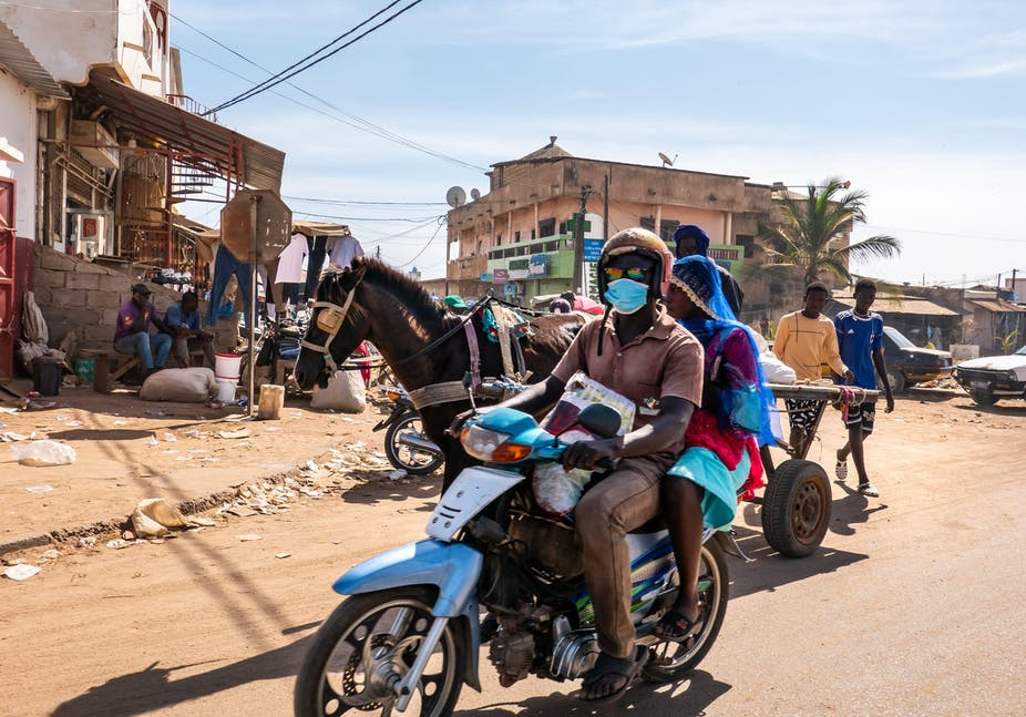 A street scene in Mbour, Senegal featuring a man and a woman on a scooter and a horse-drawn cart.