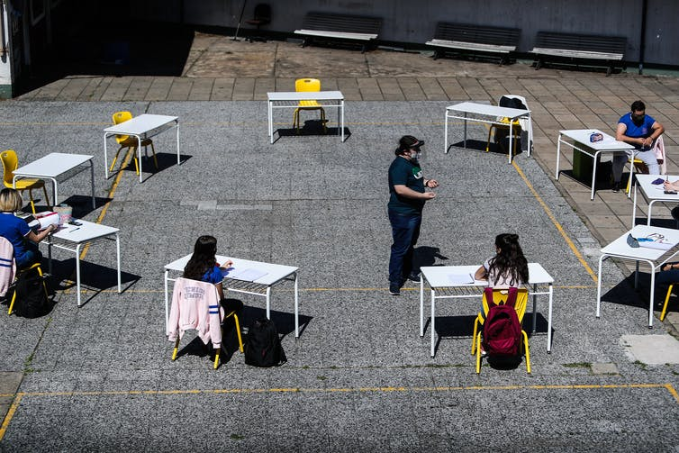 School children sit at desks arranged in a circle outdoors in Buenos Aires.