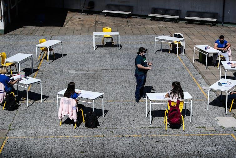 Des écoliers sont assis à des pupitres disposés en cercle en plein air à Buenos Aires