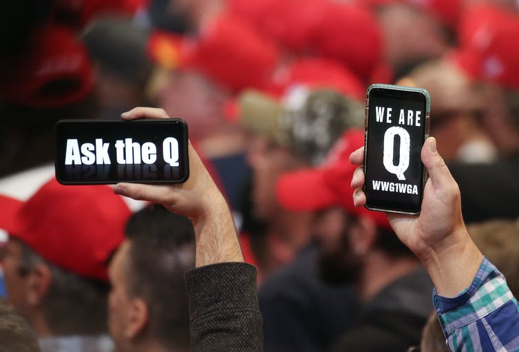 People hold up phones with the letter Q on them