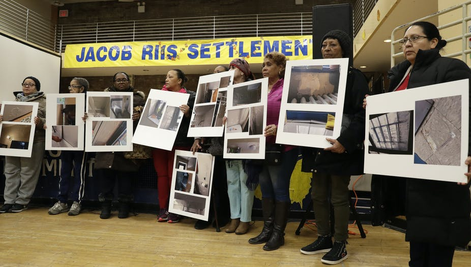 People display posters showing damaged in public housing.