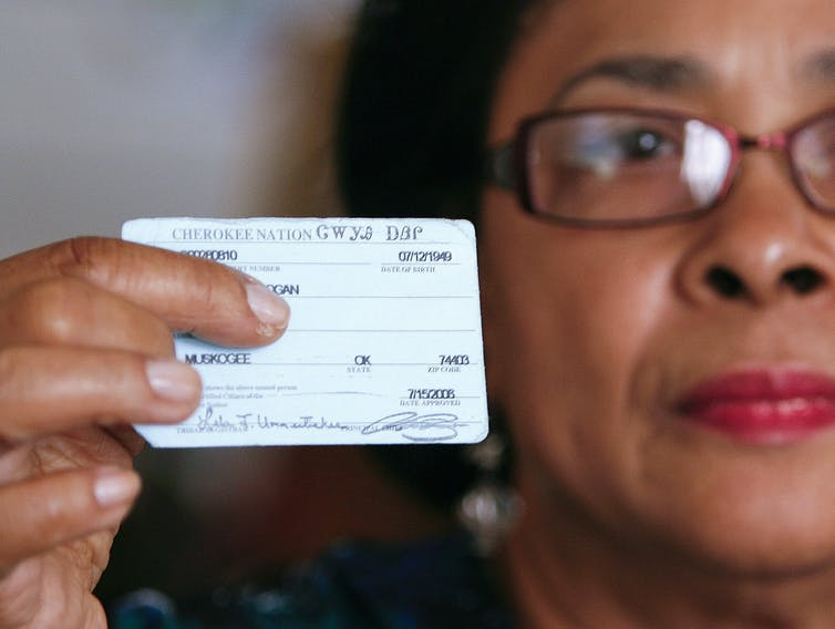 A woman who descends from Cherokee Freedmen holding her tribal ID card.