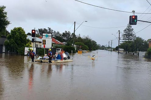 An emergency services rescue boat evacuates people along the flooded street of a town