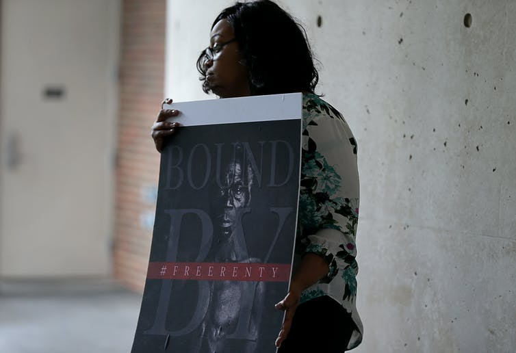 woman holds historical photo of enslaved Black man
