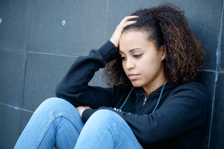 Young sad girl sitting against a wall.