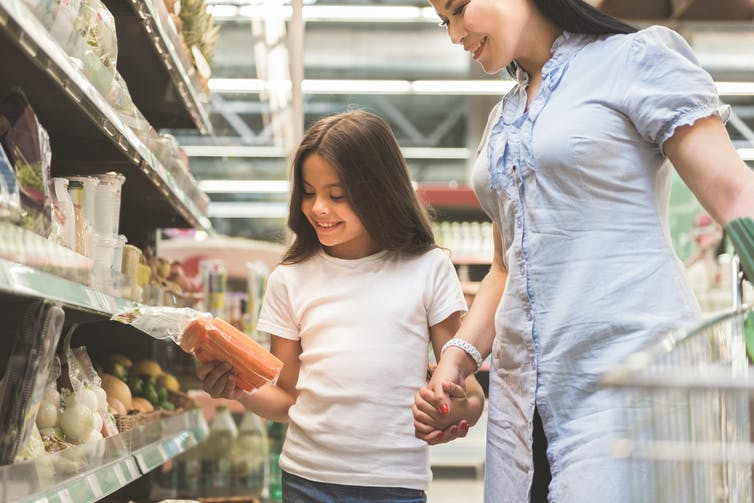 Mother and daughter looking at something in supermarket aisle.