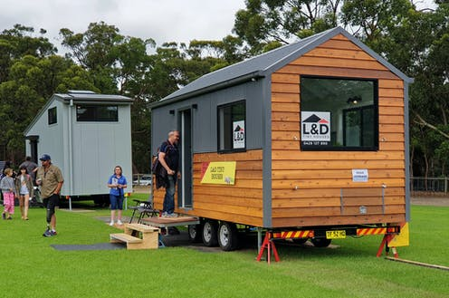 people inspecting a tiny house