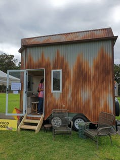women looks inside a tiny house on display