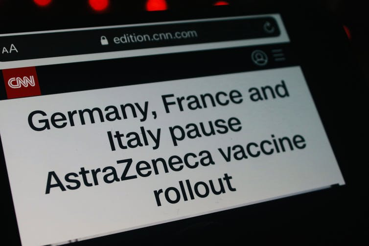 Vaccine news about vaccine pause on smartphone screen
