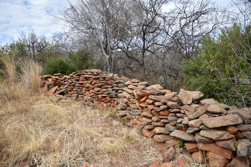 Orderly piles of stones and rocks line an area surrounded by trees and grasses