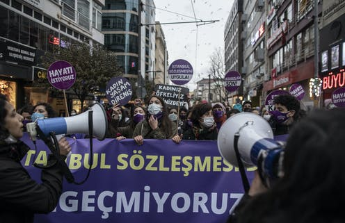 Turkish women demonstrate in the streets of Istanbul carrying banners and holding megaphones.