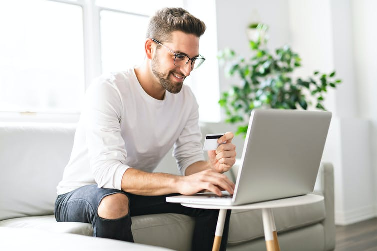 Image of a man sitting in front of his laptop.