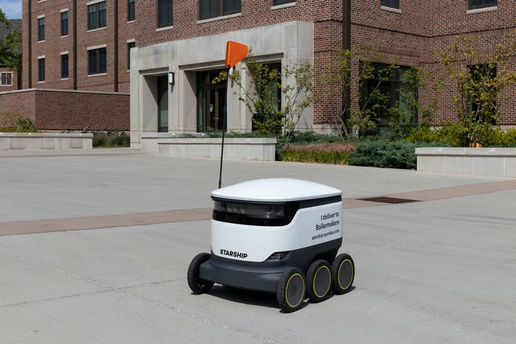 A small trolley-like robot with a flag on a city street.
