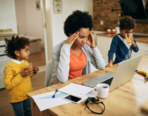 A Black woman in front of her laptop looking stressed as two children drink juice